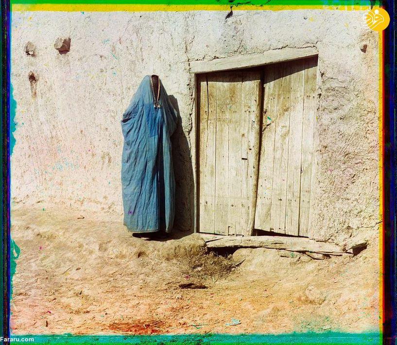 زنی برقعپوش در جلوی منزلی در سمرقند.