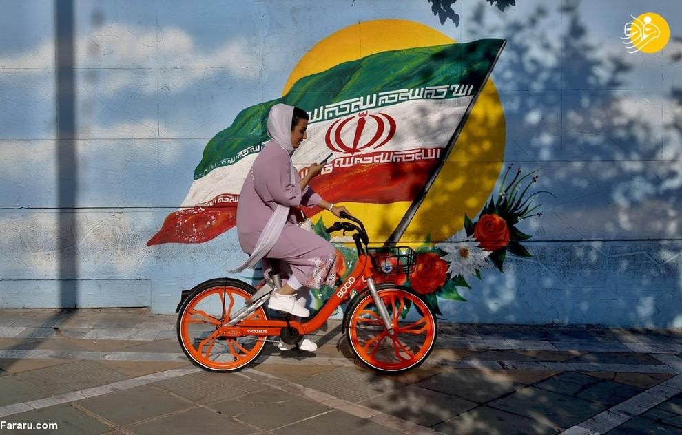یک زن ایرانی در حال دوچرخه سواری در مقابل یک نقاشی دیواری از پرچم ایران/ عکس:EPA