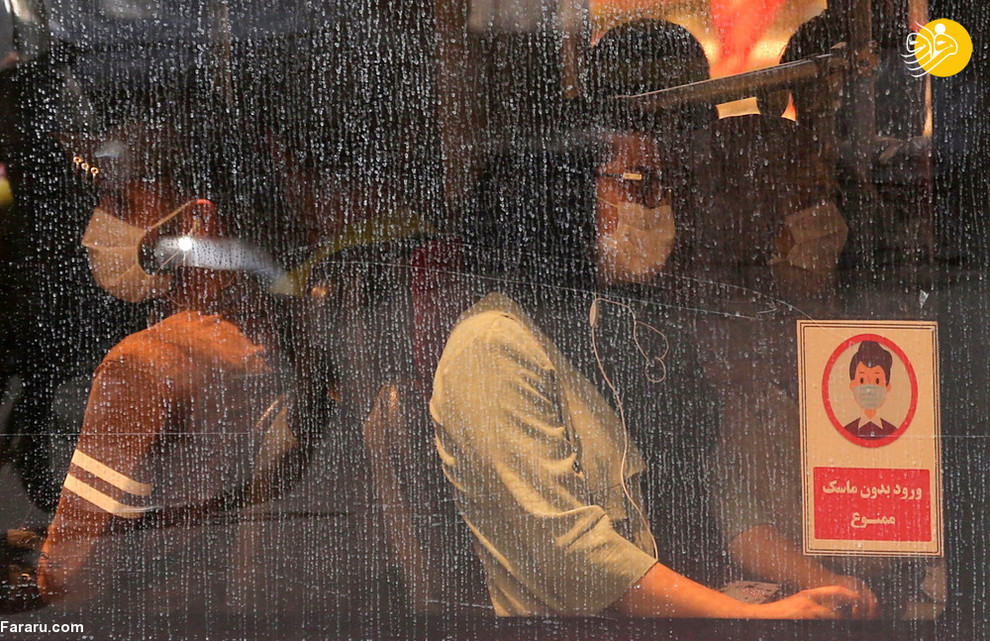 مسافران با ماسک در اتوبوس درون شهری تهران/ عکس: AFP