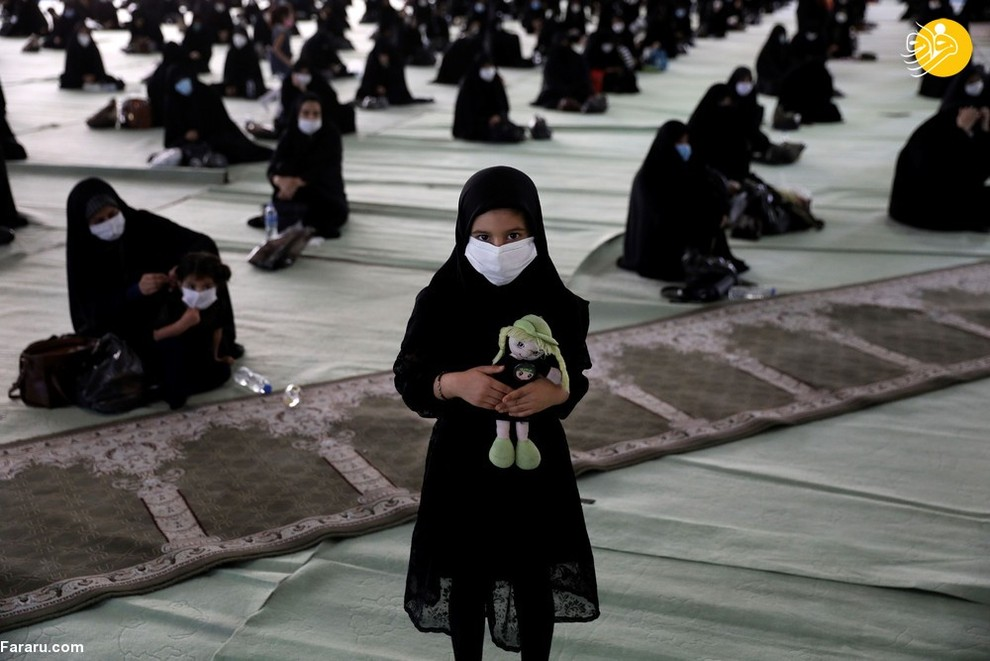 دختری با ماسک و عروسک در مراسم عزاداری شهادت امام حسین(ع) در مصلی تهران/ عکس: AP